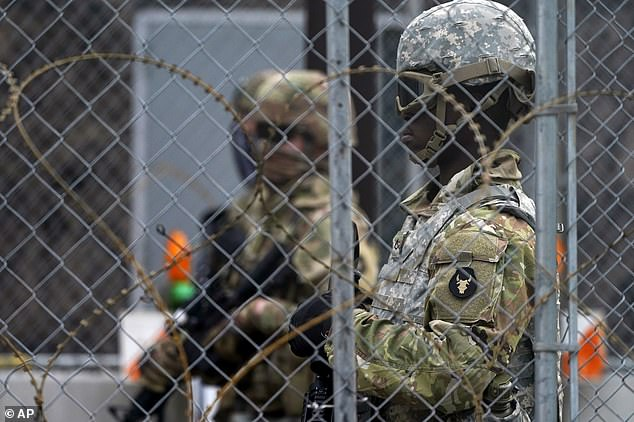 National Guard members are seen through fencing and wire near the Minneapolis Police 3rd Precinct in Minneapolis