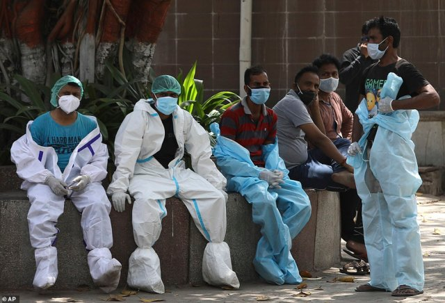 Health workers rest in between cremating virus victims in Delhi amid the huge surge in infections and deaths