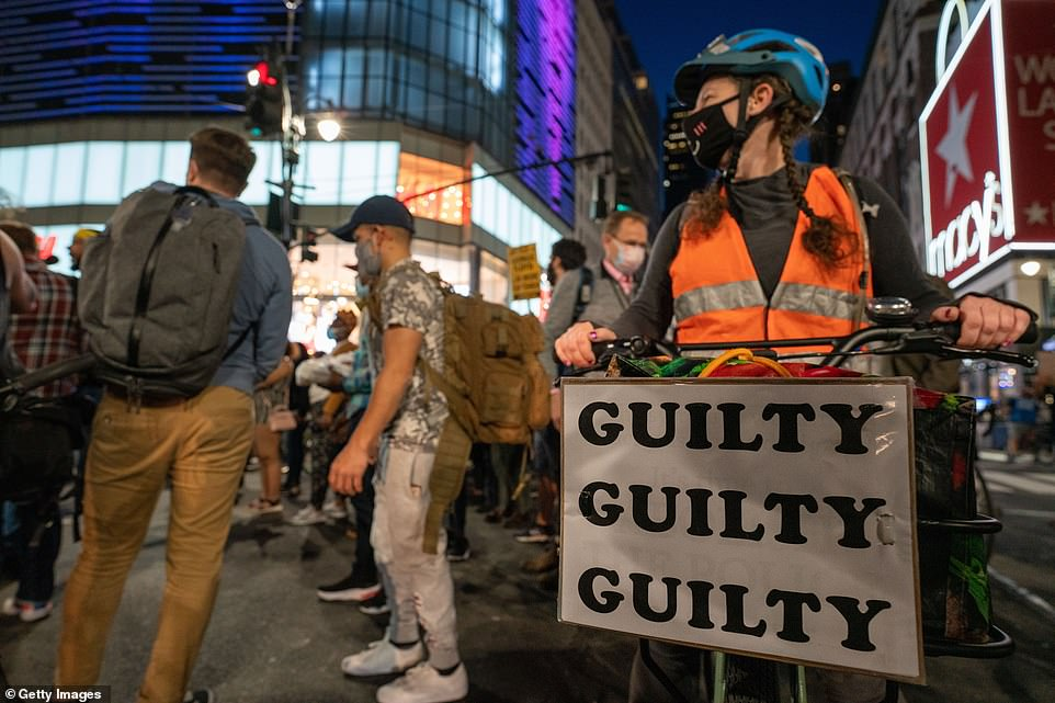 NEW YORK CITY: A woman with a sign on her bike reading, 'Guilty, guilty, guilty,' after the verdicts were delivered on Tuesday