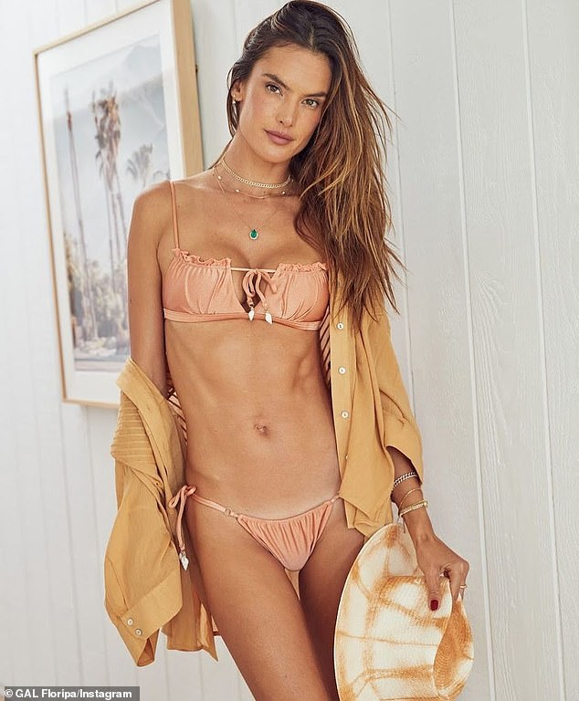 Coordinated: She slipped into the 'pink' color of the shell bikini and paired it with an open gold shirt that she let seductively slip off her shoulders