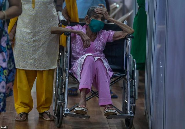 An elderly woman waits to receive a vaccine in Delhi where hospitals are running perilously low on oxygen