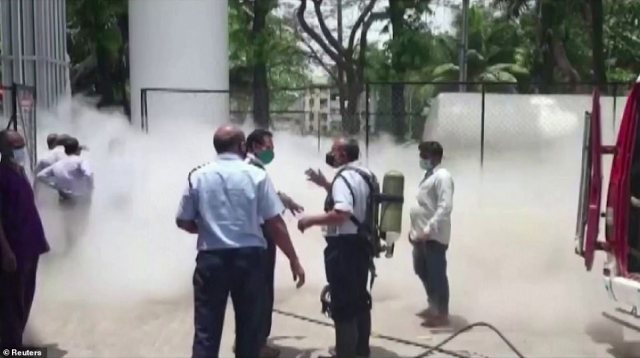 An oxygen tanker leaked outside an Indian hospital, killing 22 Covid-19 critically ill patients after their supply was shut off. Pictured: Firefighters arrive on the scene wearing protective gear
