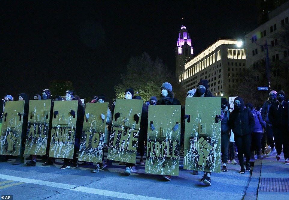 Demonstrators march through downtown Columbus on Wednesday night holding large signs reading 'All power to the people'