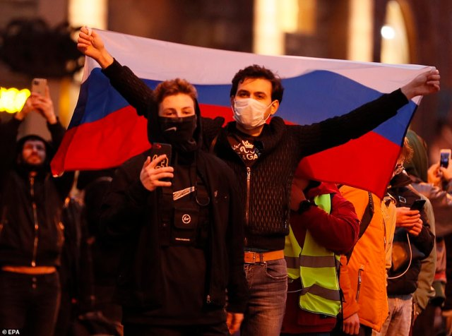 A man holds a Russian flag during an opposition rally in Moscow.Police said 6,000 people protested illegally in Moscow, while Navalny's YouTube channel said turnout in the capital was up to 10 times higher