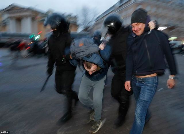 Heavily-armoured police officer wielding batons drag two protesters from the crowd in St Petersburg on Wednesday