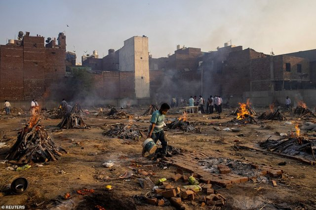 Funeral pyres of people who died from the coronavirus are seen at a crematorium ground in New Delhi on Thursday