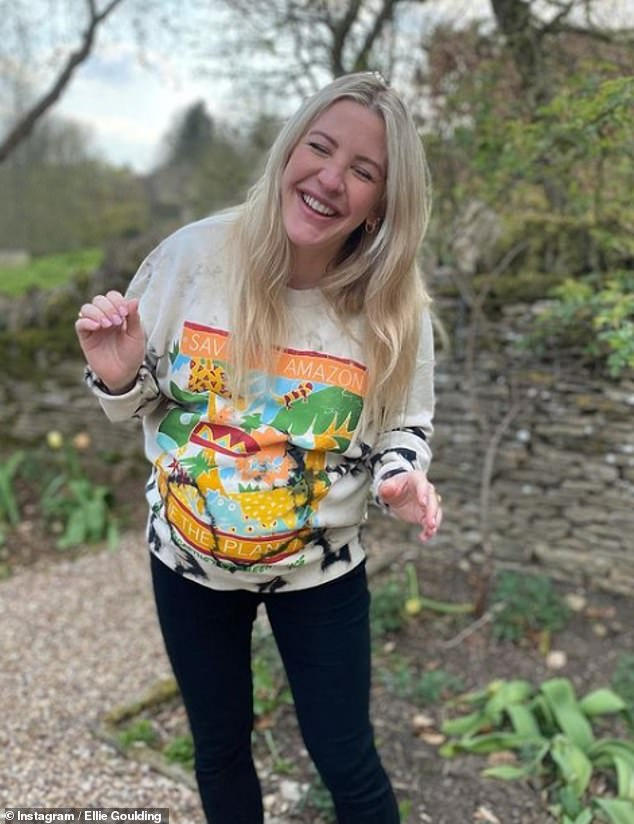 Cheery: The musician, 34, cradled her baby bump in the cosy sweatshirt, which was emblazoned with the words: 'Save our amazon, save the planet'