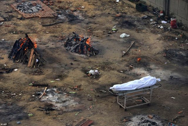 Multiple funeral pyres of those patients who died of COVID-19 disease are seen burning at a ground that has been converted into a crematorium