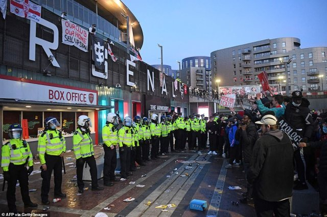 A line of police face supporters as they protest against Arsenal's US owner Stan Kroenke, outside English Premier League club Arsenal's Emirates stadium in London on April 23, 2021
