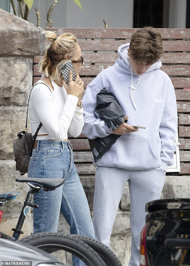 Stylish:Edwards wore blue jeans and a white crop top as she chatted on the phone