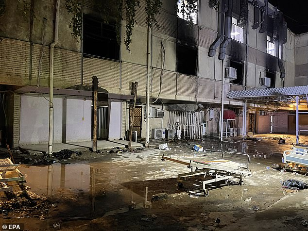 The aftermath of the fire shows burned windows and wreckage strewn on the floor below