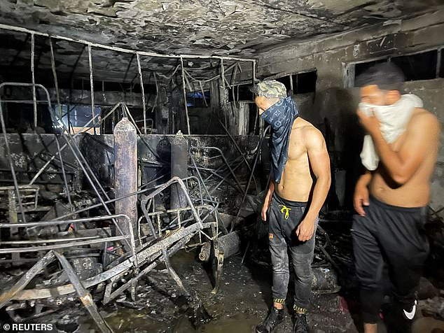 Rescuers look at the carnage caused by the oxygen tank explosion at the hospital in Baghdad