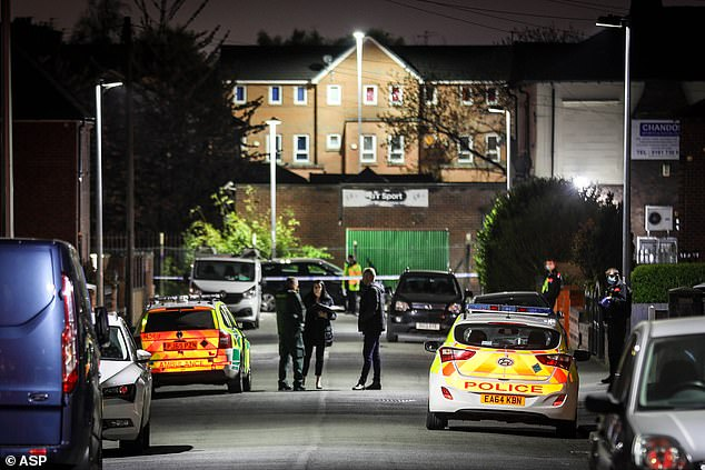 Police are pictured at the scene in Salford after a murder investigation was launched on Wednesday