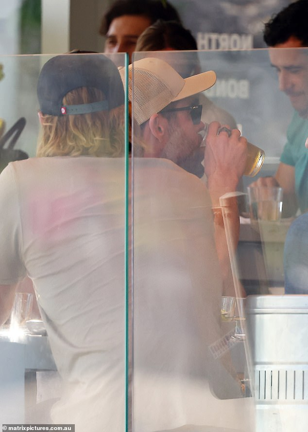 Wish you were beer: Chris was spotted sipping on a beer as he sat at a table with his friends outside the restaurant