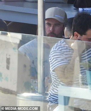 Thirsty work: Sitting at an outdoor table with a group of male friends, including Aaron, 37, Chris contentedly sipped on a schooner