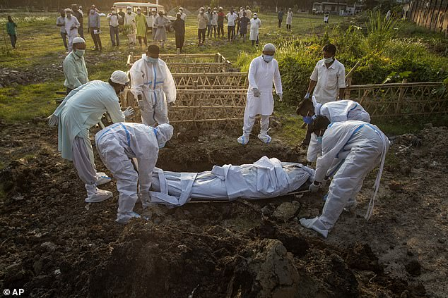 Pictured:Municipal workers prepare to bury the body of a person who died of COVID-19 in Gauhati, India, Sunday, April 25, 2021.Overcrowded hospitals in Delhi and elsewhere are being forced to turn away patients after running out of supplies of oxygen and beds