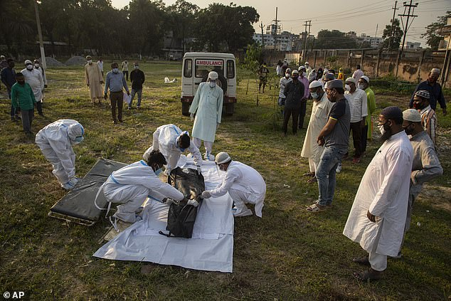 Relatives and municipal workers prepare to bury the body of a person who died of COVID-19 in Gauhati, India, Sunday, April 25, 2021.vital life-saving oxygen is in short supply and countries including Britain, Germany and the United States pledged to send urgent medical aid to help battle crisis collapsing India's tattered healthcare system