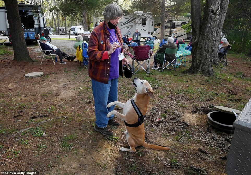 Dressed in a check shirt and blue jeans, Myrt Yarbroughgives a treat to her dog Lucky during the camping weekend, while other modern nomads sit together in a circle in the background.'We want women to develop skills and friendships in that special atmosphere of a women-only space', said the organizers on their website