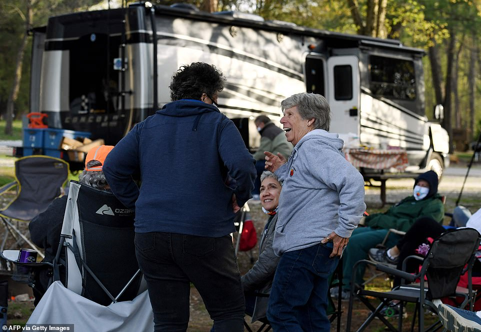 Rue Watson (pictured left) and a beaming Sandi Muller (pictured right) talk to each other while standing next to the RVing Women's circle of chairs at theRamblin Pines campsite