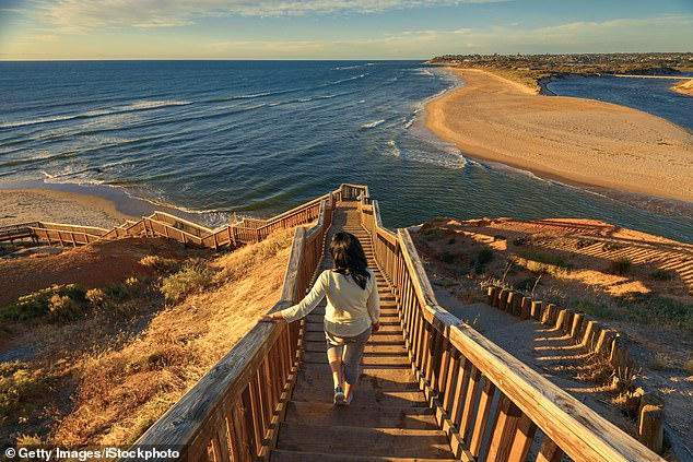 The South Australian government has announced a fourth round of tourism vouchers will be up for grabs from late May. Pictured: A  woman walking down iconic Port Noarlunga boardwalk in South Australia