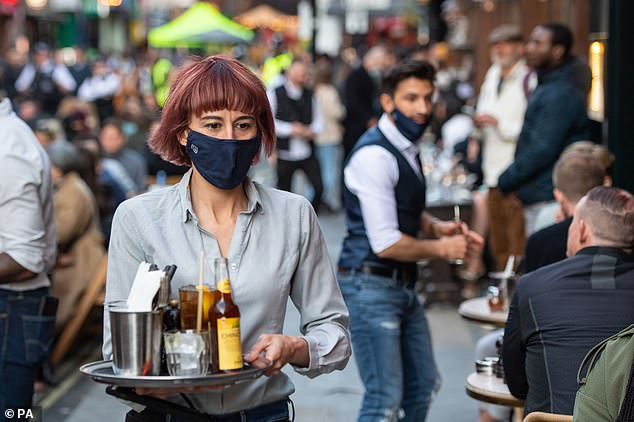 Pictured: Waiters serve people eating and drinking at outside tables on Saturday in Soho