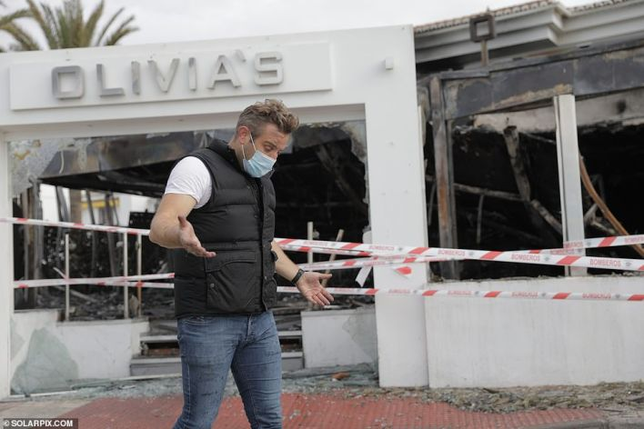 TOWIE star Elliott Wright's Spanish restaurant has been gutted in a mystery fire just weeks after his father died from coronavirus. He is pictured surveying the scene of the fire this morning