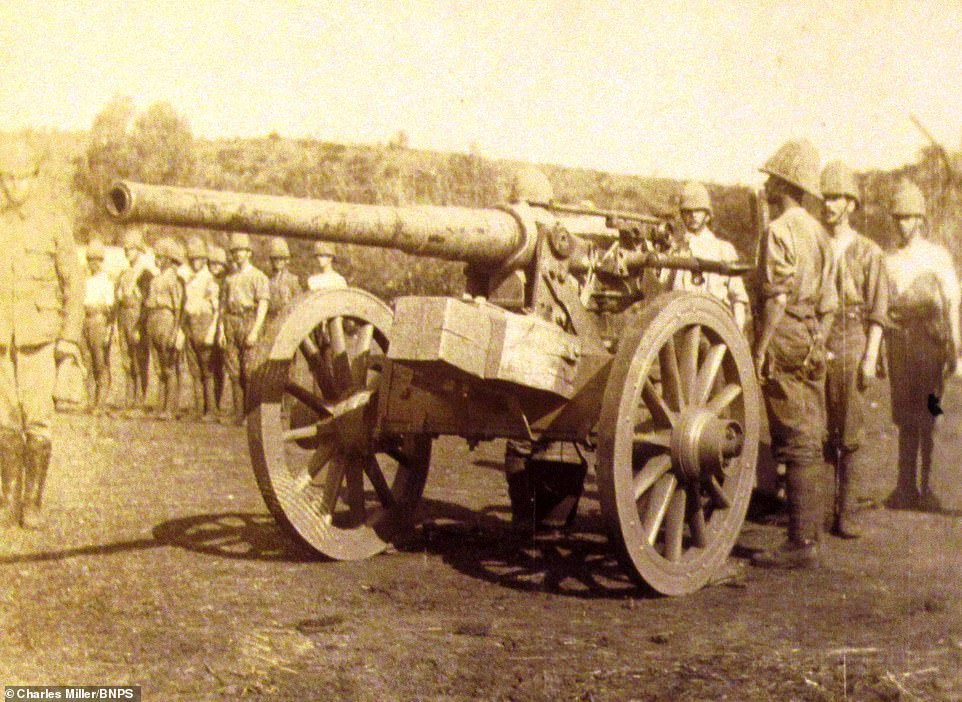 One of the guns is seen close-up as soldiers stand immediately behind it and others are seen lined up in the background