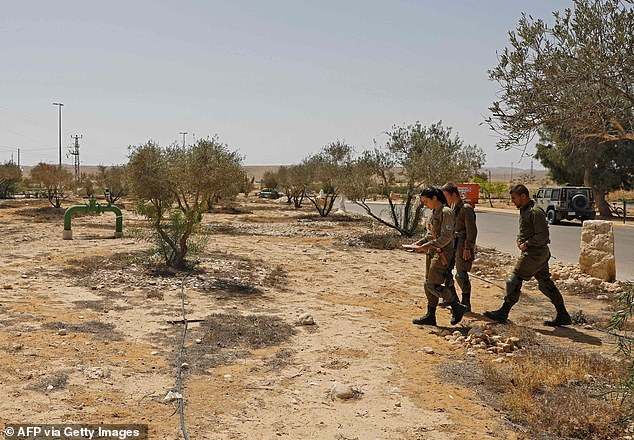 Israeli soldiers search for debris after a missile launched from Syria landed near the Dimona nuclear site in Israel's southern Negev desert, on April 22, 2021. Multiple defense batteries in Syria were struck by Israeli forces, the military said, after a missile targeted a village near a secretive nuclear site in southern Israel
