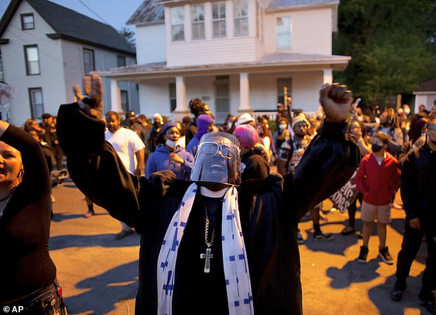 Hundreds of demonstrators, including Rev. Raymond Johnson, protested on Monday night