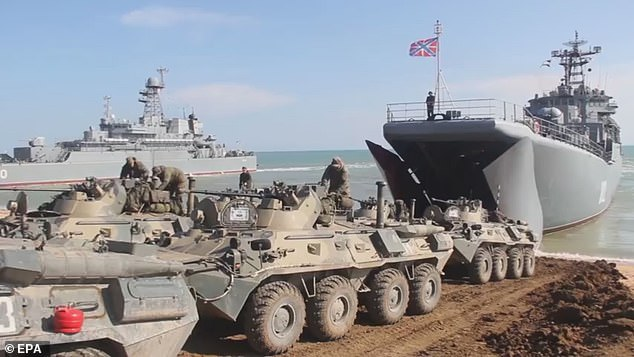 Russian armored military vehicles roll into a Russian Navy large landing ship on Friday after the military drills of the Russian Armed Forces at the Opuk range in Crimea