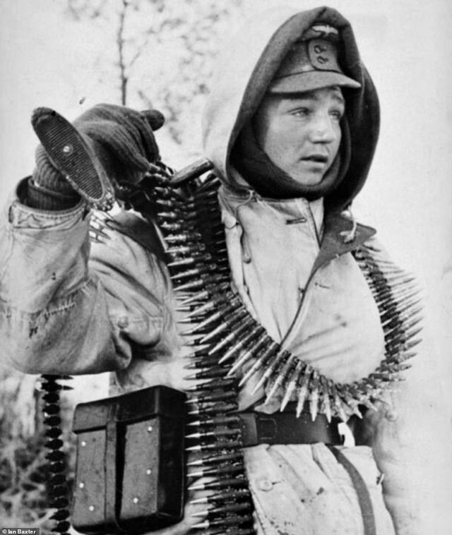 A young gunner is seen draped in bullets for his MG machine gun. He is wearing his leather infantry belt which is fitted with the tool box for his weapon. His gun is resting on his shoulder. As well as being battered by Soviet troops, the Germans were also being attacked by Ukrainian nationalists and members of the Polish resistance. They were also under immense pressure from Hitler to put their lives on the line for every yard of land