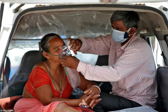 Nanduba Chavda sits in an ambulance as her husband adjusts her oxygen mask while waiting to enter a COVID-19 hospital in the city of Ahmedabad