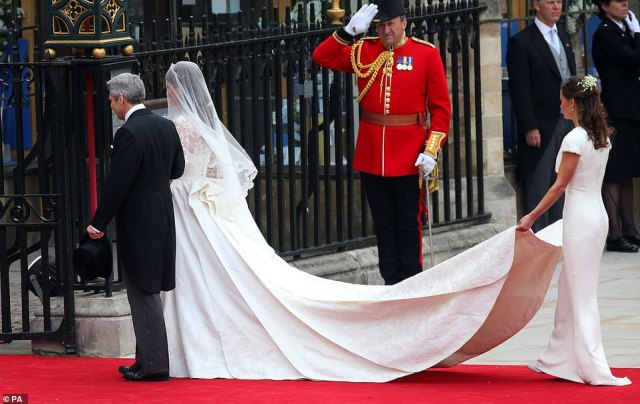 Love train: Kate Middleton arriving at Westminster Abbey with her father Michael and sister Pippa, offering the crowd a first glimpse of her beautiful designer gown, which included a bodicehand-stitched by the world's best seamstresses at the Royal School of Needlework