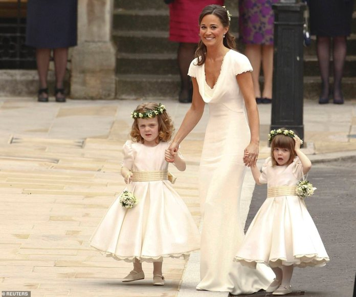 Pippa Middleton gently holds the hands of Kate's flower girls - including characterfulGrace Van Cutsem, left, as they arrive at Westminster Abbey
