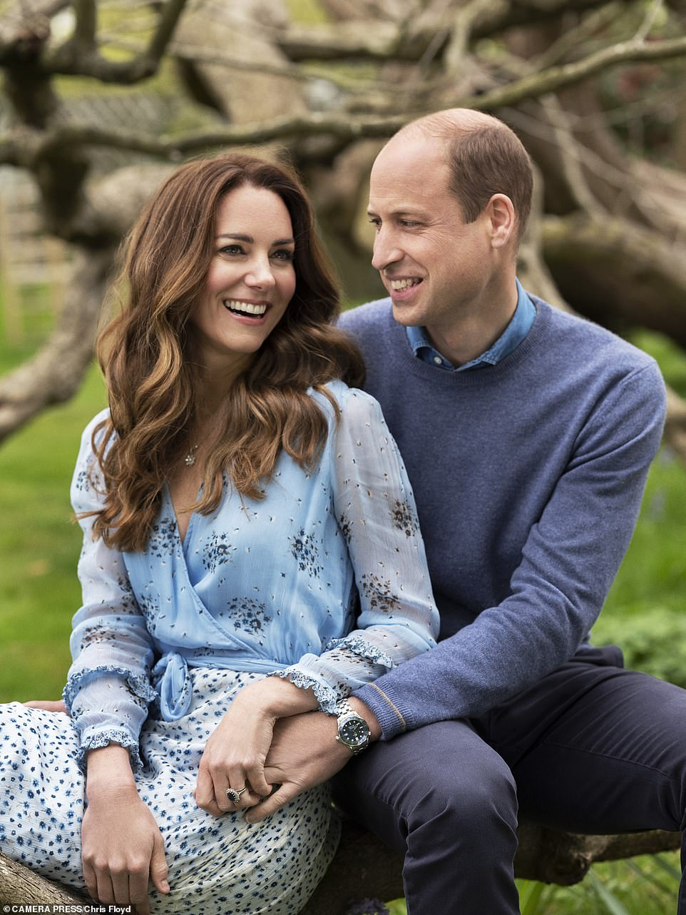 Tender moment: Kate and William hold hands in a new image captured in the garden at Kensington Palace. Pictured, Kate opted for a £195 bohemian-style blue patterned wrap dress by Ghost, while Prince William donned a familiar blue jumper and shirt