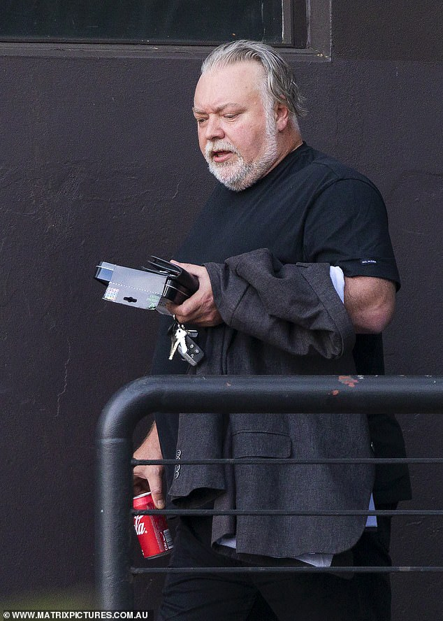 Business mind: Radio host Kyle Sandilands appeared to be discussing important matters while taking a walk near his office in Sydney's Potts Point on Wednesday