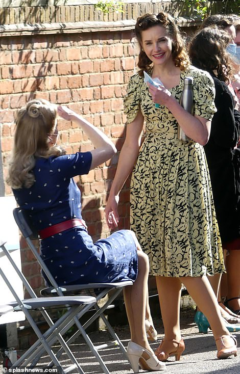 Gorgeous: One star sported an elegant yellow printed floral dress as she chatted to another female star