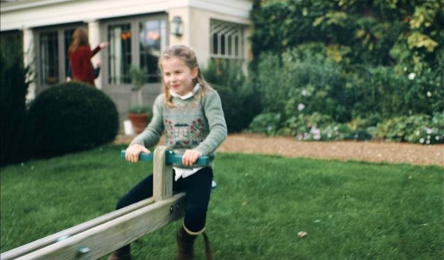 Princess Charlotte looks focused on the other end of the seesaw as she plays with her brother with the adults in the background