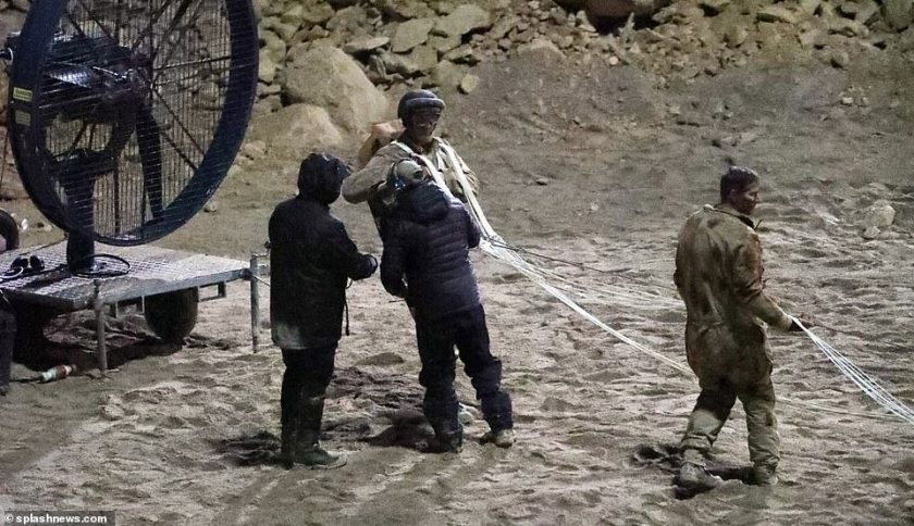 Upping the stakes: Jack and another actor were seen having their parachutes checked before another take, and a large wind turbine was seen near them to make the shoot more dramatic