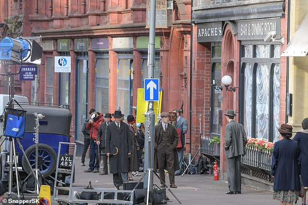 Cast and crew: Corporation Street in Birmingham had been turned into a showroom for the film as extras loitered on the street