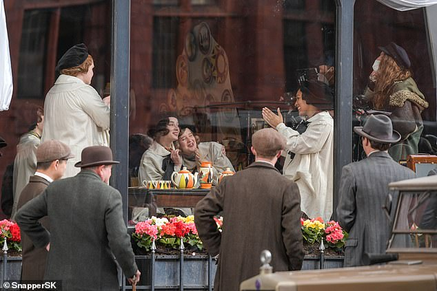 Crowds:Extras dressed in period clothing stood to watch the ladies in the window as they appeared to be having a good time