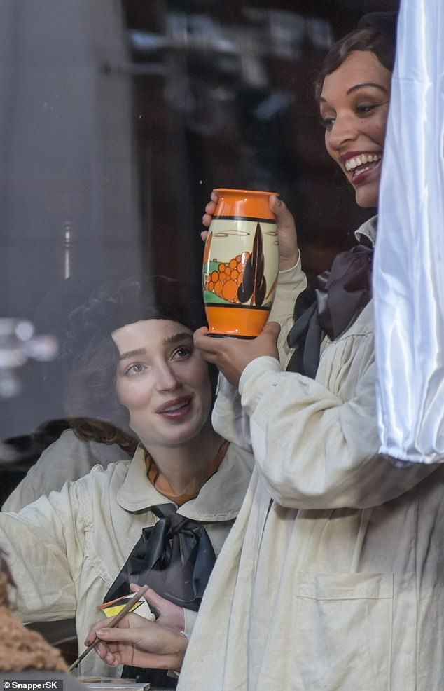 Cheerful: Laura White beams as she showcases a bright orange vase while Phoebe watches on amused