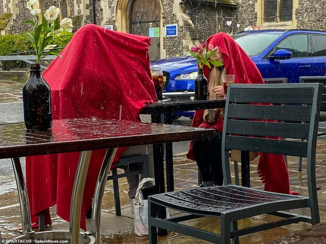 Punters huddled under blankets and coats in the wet weather with diners still forced to remain outside due to Covid restrictions