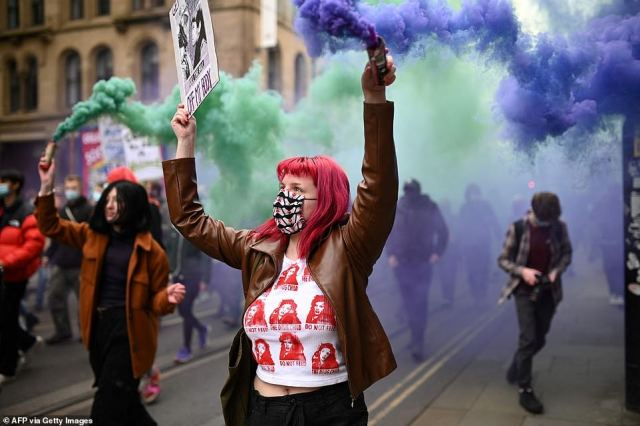 Demonstrators hold flares as they protest against the Police, Crime, Sentencing and Courts Bill in central Manchester today