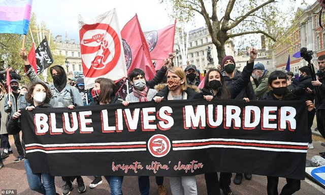 A group of demonstrators hold up a banner in London earlier today and are followed by a number of people waving flags