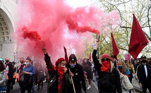 Re flares are held in the air by these two women in the middle of a crowd of Kill the Bill demonstrators in London earlier today
