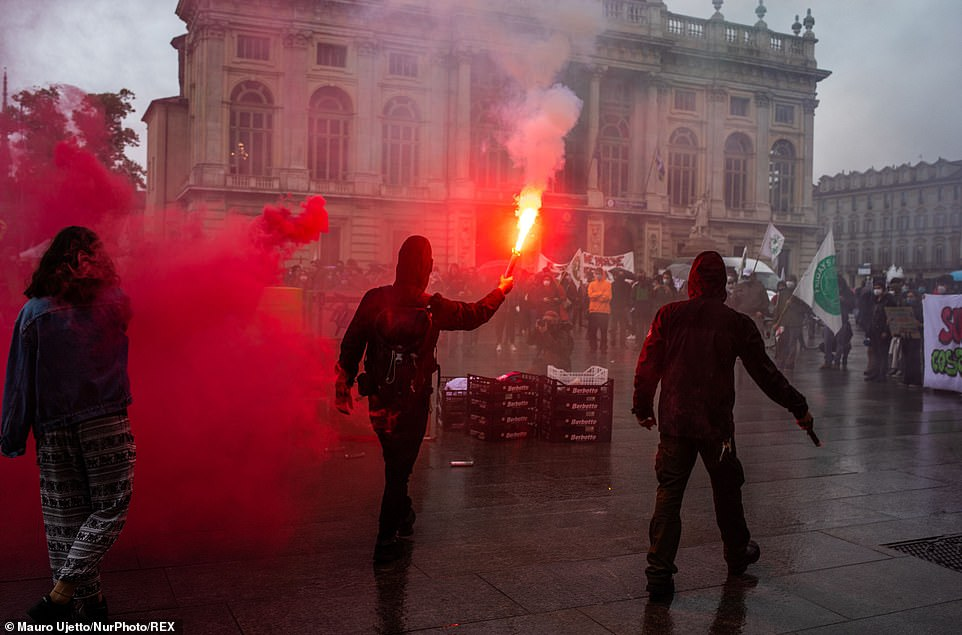 TORINO, ITALY: A hooded figure holds a red flare in the air during the May Day protests in Italy earlier today
