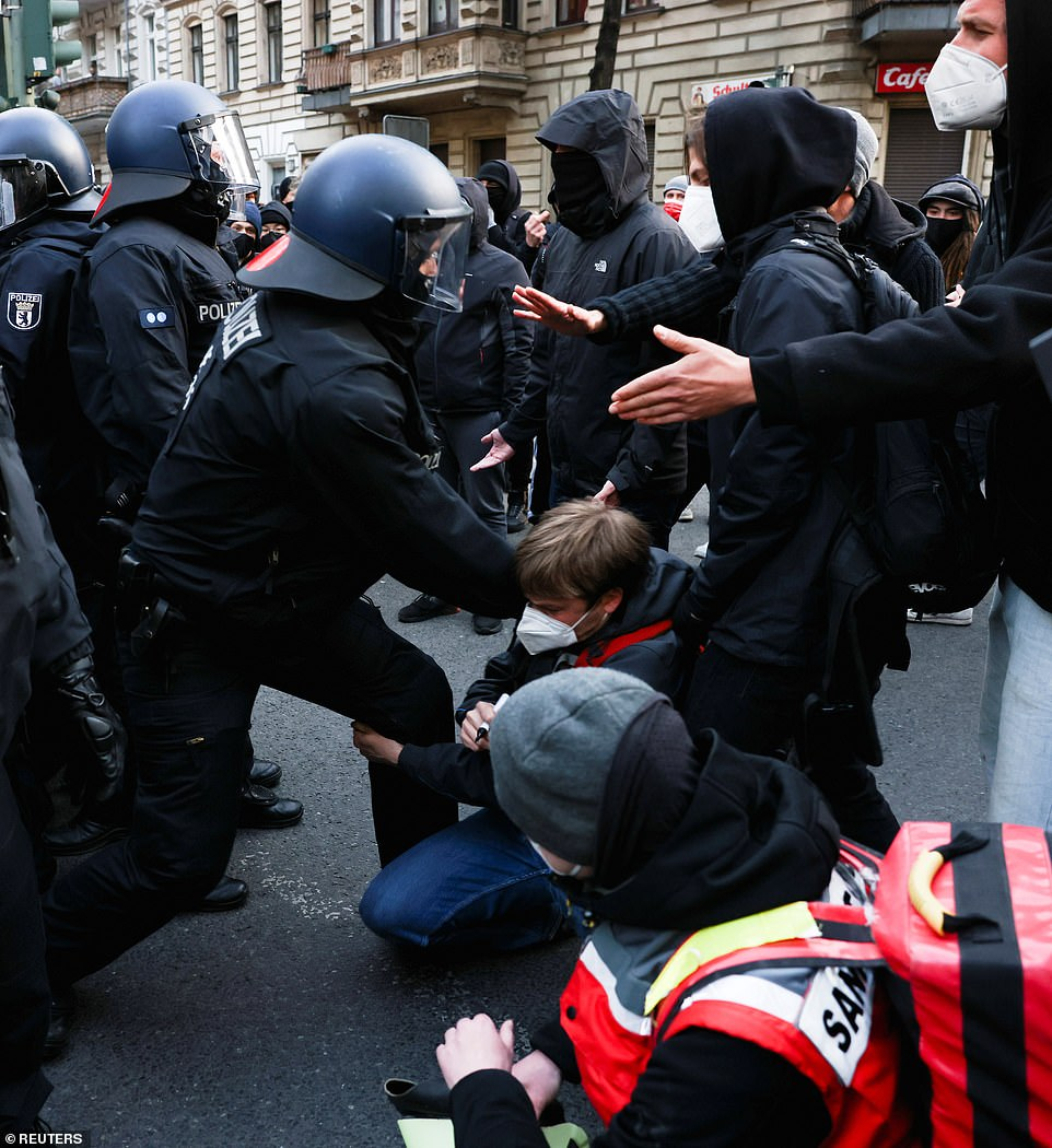 BERLIN, GERMANY: A demonstrator in Berlin grabs hold of the leg of a police officer today during the May Day protests