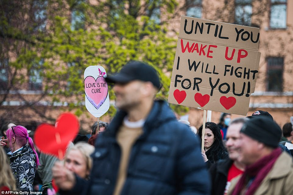 STOCKHOLM, SWEDEN: Signs which read 'Love is the cure' and 'until you wake up, I will fight for you!' are held in the air by demonstrators in Sweden earlier today