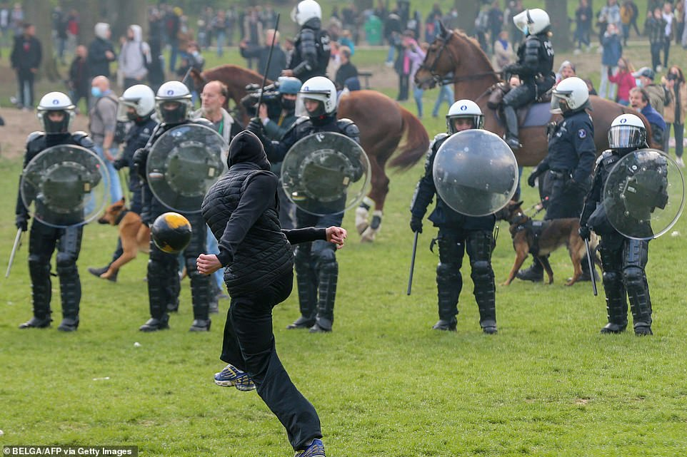 BRUSSELS, BELGIUM: A protestors kicks a football towards a line of police officers at a park in Belgium earlier today during a May Day protest